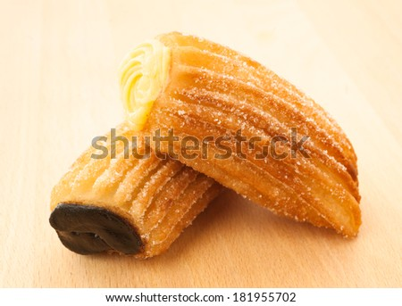 Churros filled with cream and chocolate on wood