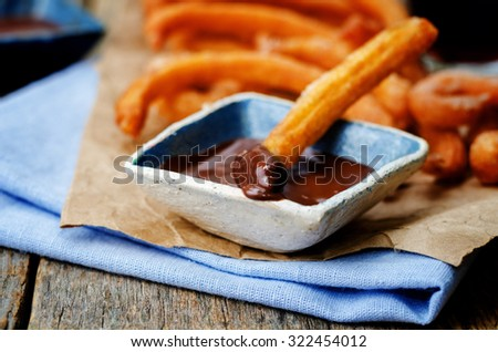 churros with chocolate sauce on a dark wood background. toning. selective focus - stock photo