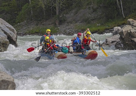 "CHUYA RIVER, RUSSIA - AUGUST 7, 2014: Sports catamaran in the middle of a difficult rapids. River Chuya, Altai. Tourists call this rapids as ""Horizon"""
