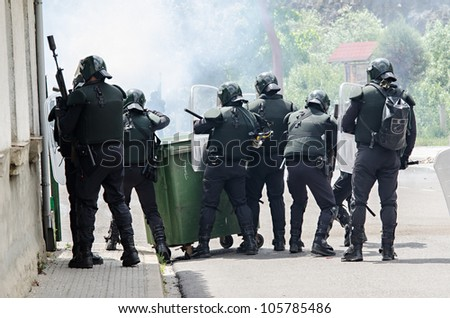 CIÑERA, SPAIN - JUNE 19:  Anti riot police agents of the Guardia Civil disperse striking miners shooting rubber balls and smoke cans on June 19th 2012 in Ciñera, Spain. - stock photo