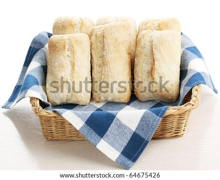 ciabatta bread in a wicker basket with white and blue napkin - stock photo