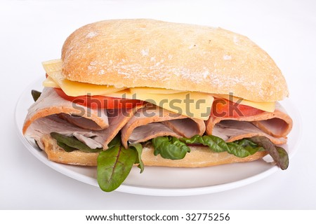 Ciabatta bread sandwich stuffed with meat,cheese and vegetables on a plate - stock photo