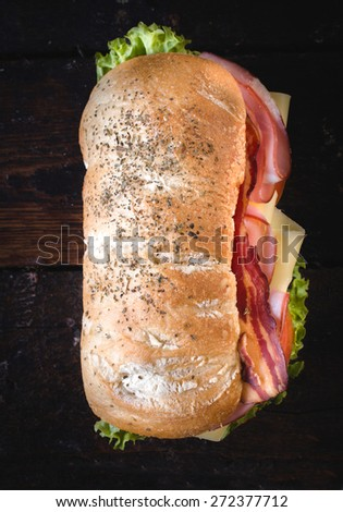 Ciabatta sandwich with bacon and cheese on wooden background from above,selective focus  - stock photo