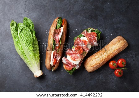 Ciabatta sandwich with romaine salad, prosciutto and mozzarella cheese over stone background. Sandwich ingredients. Top view - stock photo