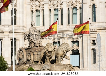 Cibeles fountain in Madrid surrounded by Spanish flags, a neoclassical marble sculpture that has become an icon of the city. - stock photo