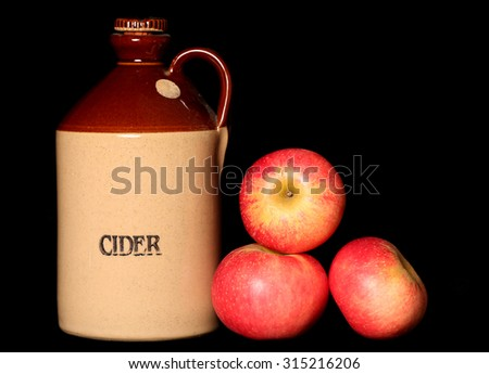 Cider jug and red apples on black background