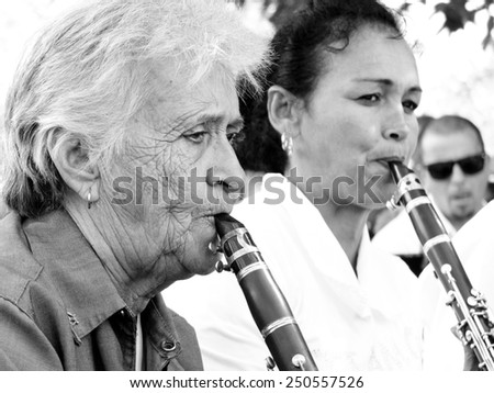 CIENFUEGOS, CUBA, DECEMBER 9: An old woman and an another musician play music in a square , on december 9, 2014 in Cienfuegos, Cuba. - stock photo