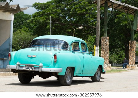 CIENFUEGOS, CUBA - JUNE 21, 2015: Green american vintage car parked on the street in the countryside