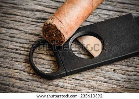 Cigar and Cigar Cutter on Rustic Wood Background - stock photo