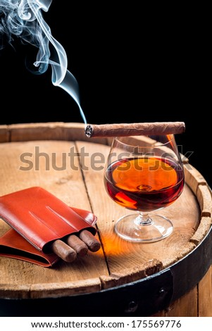 Cigar and cognac on black background with old barrel - stock photo