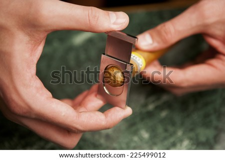 cigar and cutter in man�´s hand  - stock photo