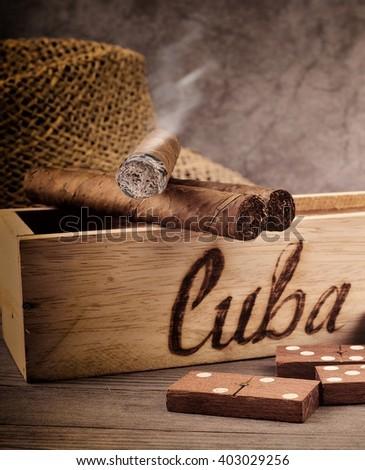 Cigar and tobacco leaf. Cigars. Cuban Cigars. Cigar production in Cuba. Cigar. Handmade cigar. Cigars, Cuba.  Cigar and domino play. Cigar still life. - stock photo
