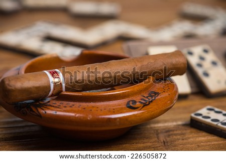 Cigar in ash tray and domino in background - stock photo
