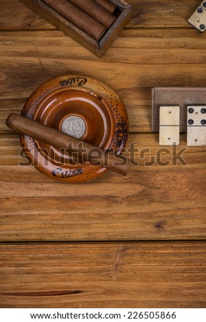 Cigar in ash tray on table - stock photo