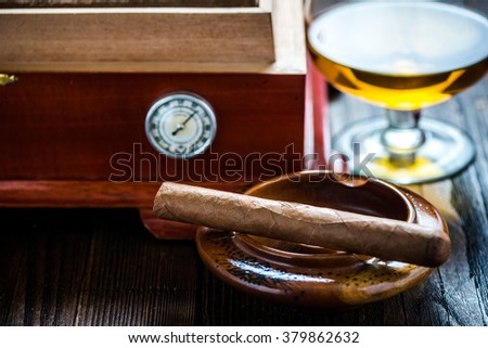 Cigar with glass of cognac and humidor on wooden table. Rich person or congratulating concept. - stock photo