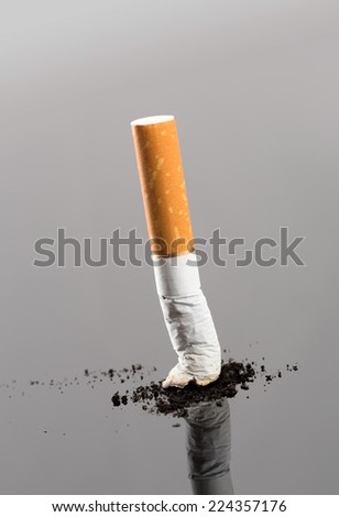 Cigarette butt with smoke on grey - stock photo