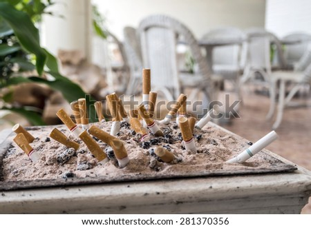 Cigarette butts in the sand - stock photo