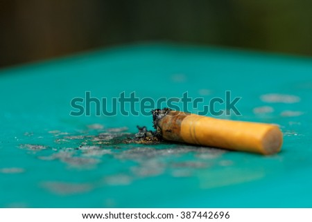 Cigarette butts on green plastic table. Concepts. - stock photo