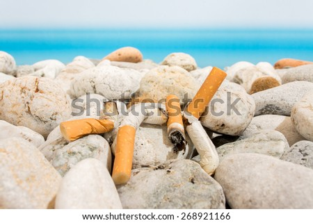 Cigarette butts on the beach - stock photo