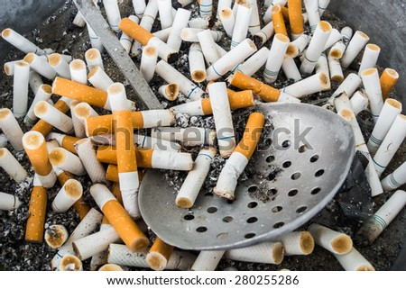 Cigarette butts with a dipper at ashtray  - stock photo