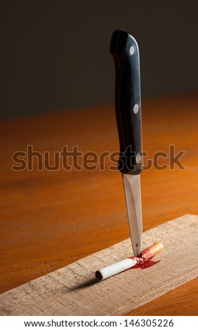 Cigarette impaled on wood and blood flow - stock photo