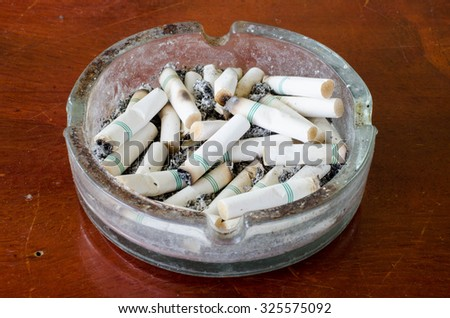 Cigarette in ashtray on table wood - stock photo