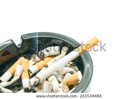 cigarette in black ashtray on white background closeup - stock photo