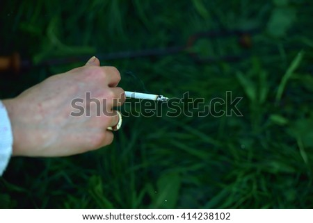 Cigarette in the hand of a woman, enjoying her cigarette in the morning on the green grass background close up. Lights and shadows. Selective focus - stock photo