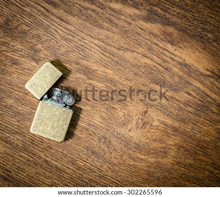Cigarette lighter on the old wooden table table. close-up. - stock photo
