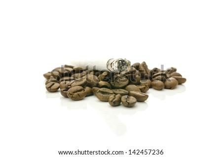 Cigarette on coffee grains. Concept of unhealthy habits. - stock photo