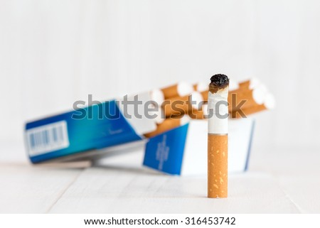 Cigarette package and butt on white wooden background - stock photo