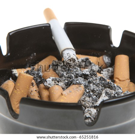 Cigarette smoking in a full ashtray. - stock photo