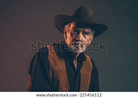 Cigarette smoking old rough western cowboy with gray beard and brown hat. Low key studio shot. - stock photo