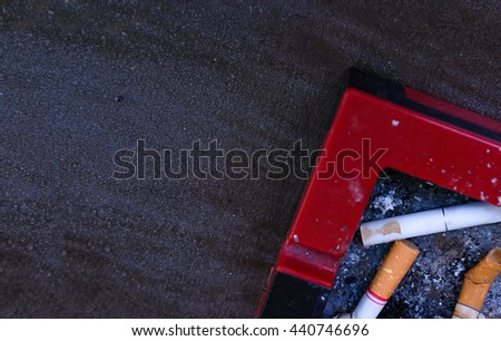 Cigarette stub in red tray - stock photo