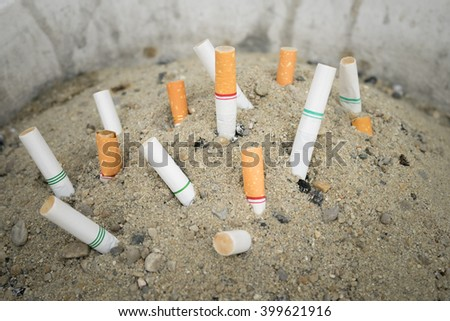 Cigarette stubs in a sand box ashtray - bad habit, cause of cancer - stock photo