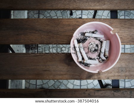 Cigarette stubs in ashtray on the wooden table with no smoking concept (light and shadow picture style) - stock photo