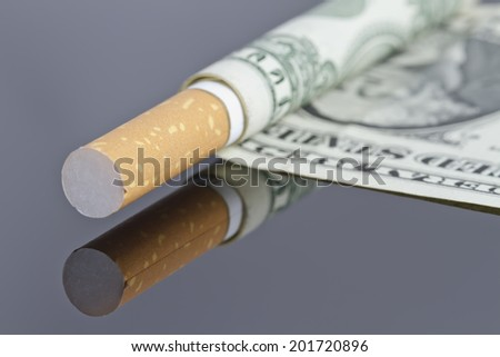 Cigarette which instead of tissue paper dollar. - stock photo