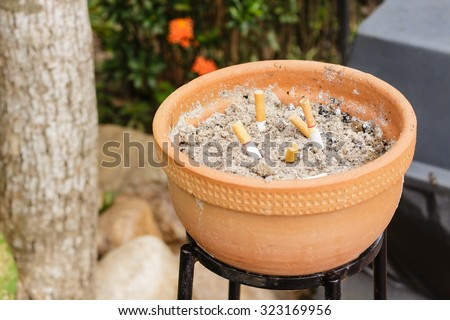Cigarette with ashtray at the park. - stock photo
