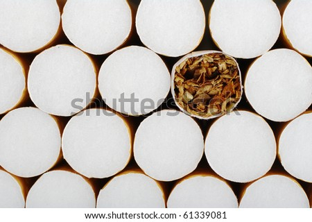 Cigarette without filter in between ones with filter as background - stock photo