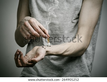 Cigarettes, addiction and public health topic: smoker puts his hand on the cigarette on a dark background - stock photo