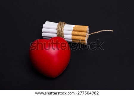 Cigarettes dynamite and heart on a black background - stock photo