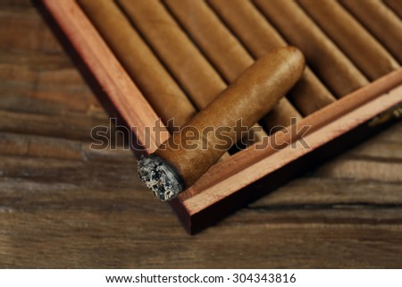 Cigars and burning one in box on wooden table, closeup - stock photo