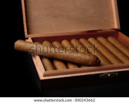 Cigars in box on black background - stock photo