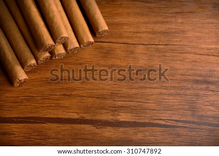Cigars on wooden background - stock photo