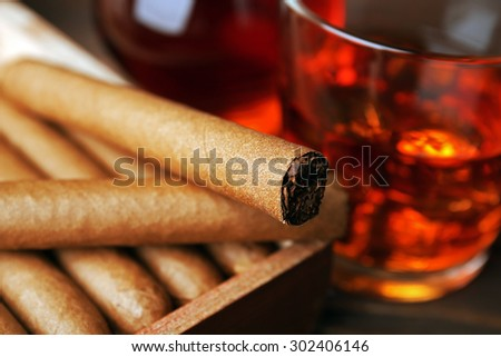 Cigars with glass of cognac on wooden table, closeup - stock photo