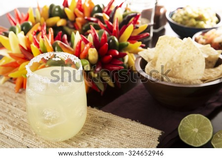Cinco de Mayo festive table with a margarita in the foreground, tortilla chips and colorful hot peppers. - stock photo
