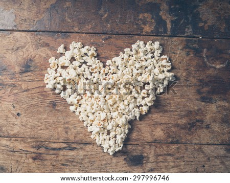 Cinema concept of popcorn arranged in a heart shape on wooden table - stock photo