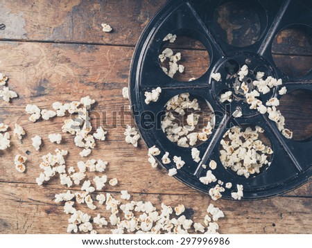 Cinema concept of vintage film reel with popcorn on wooden surface - stock photo