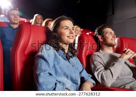cinema, entertainment and people concept - happy friends watching comedy movie in theater
