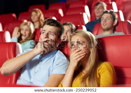 cinema, entertainment and people concept - happy friends watching horror, drama or thriller movie in theater - stock photo
